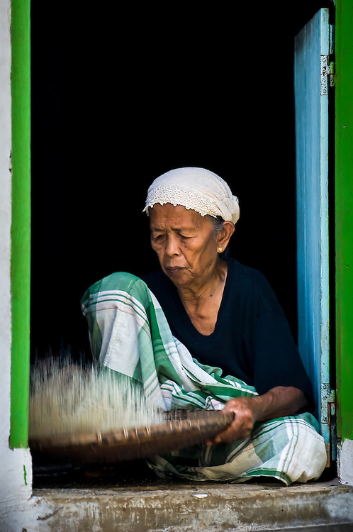 Portrait of an old lady sifting rice in a village in southern Sulawesi, Indonesia