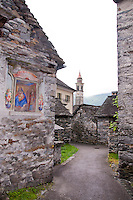Ticino, Southern Switzerland. Typical village scene in Moghegno showing traditional stone houses and narrow streets. A small fresco of the Mary and the Christ Child is painted on the exterior of one of the buildings.