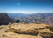 Man takes a photo sitting at the edge of the Grand Canyon  on the south rim by Pipe Creek Vista, Arizona USA. The Colorado River can be seen below.