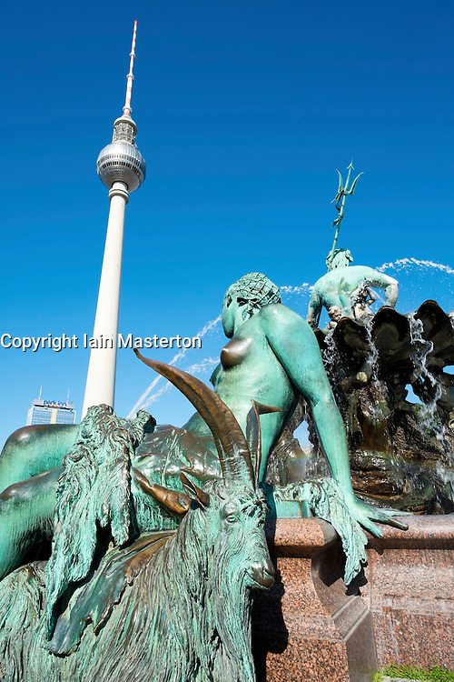 Ornate fountain with sculptures in Alexanderplatz with TV Tower to rear in Berlin Germany