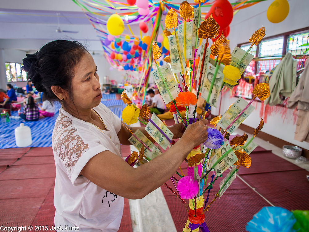 "04 APRIL 2015 - CHIANG MAI, CHIANG MAI, THAILAND: A woman donates money to a boy being ordained at the Poi Sang Long Festival in Chiang Mai. The Poi Sang Long Festival (also called Poy Sang Long) is an ordination ceremony for Tai (also and commonly called Shan, though they prefer Tai) boys in the Shan State of Myanmar (Burma) and in Shan communities in western Thailand. Most Tai boys go into the monastery as novice monks at some point between the ages of seven and fourteen. This year seven boys were ordained at the Poi Sang Long ceremony at Wat Pa Pao in Chiang Mai. Poy Song Long is Tai (Shan) for ""Festival of the Jewel (or Crystal) Sons.      PHOTO BY JACK KURTZ"
