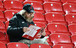 A Liverpool fan in the stands reads the programme
