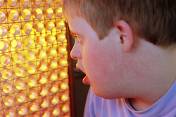 Teenage boy with Downs Syndrome looking at disco lights,