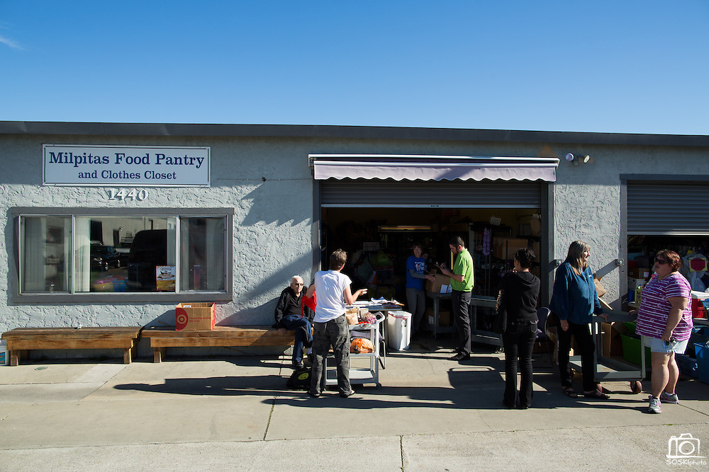 Beneficiaries wait outside as volunteers prepare Thanksgiving gifts and monthly groceries at the Milpitas Food Pantry in Milpitas, California, on November 25, 2014. (Stan Olszewski/SOSKIphoto)