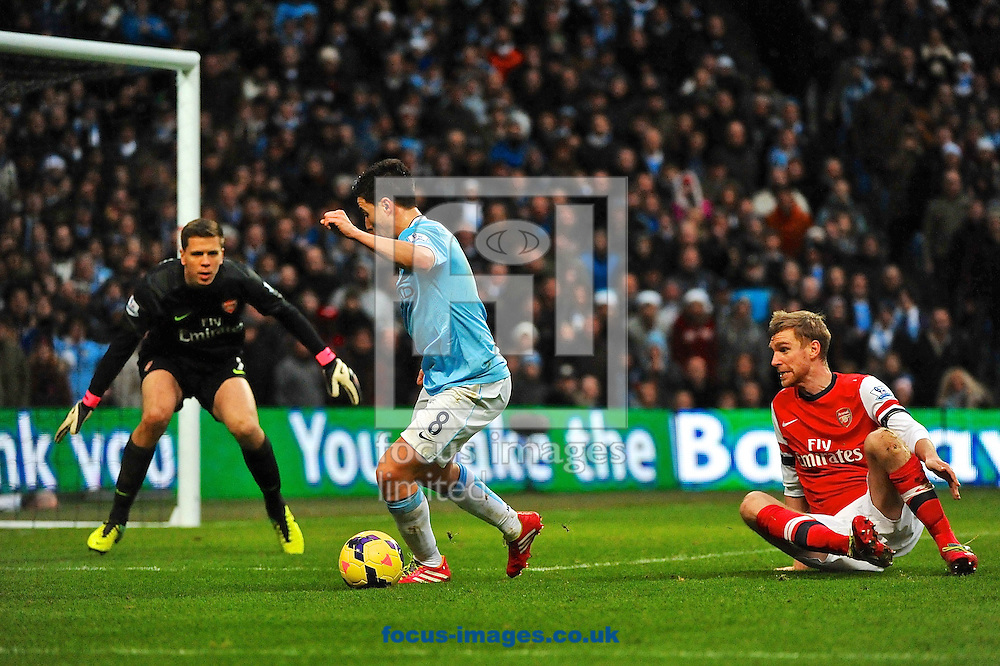 Picture by Ian Wadkins/Focus Images Ltd +44 7877 568959<br /> 14/12/2013<br /> Samir Nasri of Manchester City leaves Per Mertesacker of Arsenal on the floor and approaches the goal during the Barclays Premier League match at the Etihad Stadium, Manchester.