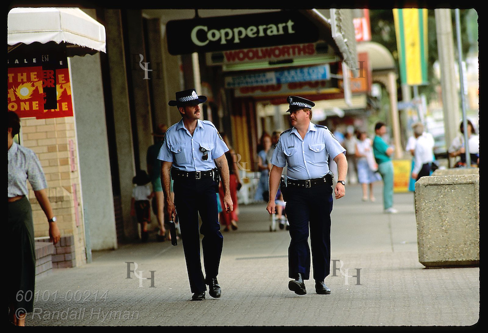 Two policemen walk beat in shopping district along main street of Wagga Wagga, New South Wales. Australia