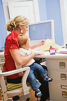 A busy mother holds her infant son in her arms while she attends to paperwork on her desk.