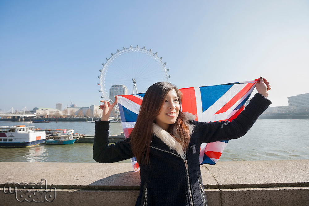 Happy woman with British flag against London Eye at London; England; UK