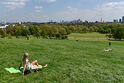 © Licensed to London News Pictures. 04/05/2018. LONDON, UK.  A woman enjoys the sunshine and warm temperatures in Primrose Hill.  Forecasters predict that the upcoming Bank Holiday Monday could see temperatures exceed 25C.  Photo credit: Stephen Chung/LNP