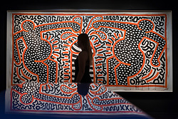 "© Licensed to London News Pictures. 28/06/2018. LONDON, UK. A gallery staff member poses against ""Untitled (May24-83)"", 1983, by Keith Haring.  Members of the public visit Masterpiece London, the world's leading cross-collecting art fair held in the grounds of the Royal Hospital Chelsea.  The fair brings together 160 international exhibitors presenting works from antiquity to the present day and runs 28 June to 4 July 2018.  Photo credit: Stephen Chung/LNP"