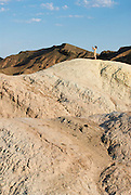 A lone woman stands atop the rocks at Zabriskie Point in Death Valley National Park with a camera taking pictures.