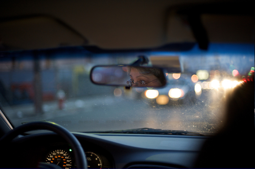 Picture of woman driving in rain with her glance visible in the rearview mirror. Viewpoint from back seat.