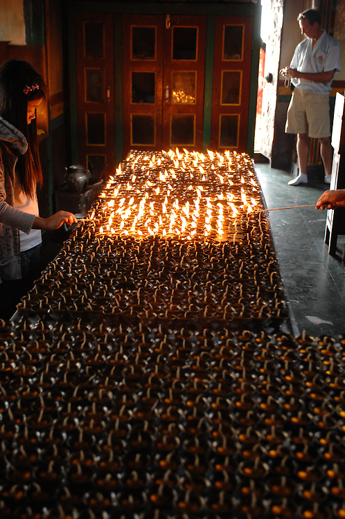 Prayer candles being lit at a Buddhist temple at Swayambhunath - the Monkey Temple - in Nepal.