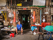 20 APRIL 2013 - BANGKOK, THAILAND:   A man sits in front of his 100 years old traditional style Chinese home in Talat Noi (Talat means Market, Noi means Small. Literally Small Market). The Talat Noi neighborhood in Bangkok started as a blacksmith's quarter. As cars and buses replaced horse and buggy, the blacksmiths became mechanics and now the area is lined with car mechanics' shops. It is one the last neighborhoods in Bangkok that still has some original shophouses and pre World War II architecture. It is also home to a  Teo Chew Chinese emigrant community.   PHOTO BY JACK KURTZ