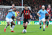 Adam Smith (15) of AFC Bournemouth brings the ball out with Raheem Sterling (7) of Manchester City and Sergio Aguero (10) of Manchester City chasing during the Premier League match between Bournemouth and Manchester City at the Vitality Stadium, Bournemouth, England on 2 March 2019.