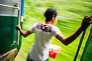 15 JUNE 2013 - YANGON, MYANMAR:  A vendor leans out of the Yangon Circular Train as it rolls through the countryside. Yangon Circular Railway is the local commuter rail network that serves the Yangon metropolitan area. Operated by Myanmar Railways, the 45.9-kilometre (28.5mi) 39-station loop system connects satellite towns and suburban areas to the city. The railway has about 200 coaches, runs 20 times and sells 100,000 to 150,000 tickets daily. The loop, which takes about three hours to complete, is a popular for tourists to see a cross section of life in Yangon. The trains from 3:45 am to 10:15 pm daily. The cost of a ticket for a distance of 15 miles is ten kyats (~nine US cents), and that for over 15 miles is twenty kyats (~18 US cents). Foreigners pay 1 USD (Kyat not accepted), regardless of the length of the journey.     PHOTO BY JACK KURTZ