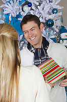 Man handing woman present in front of Christmas tree