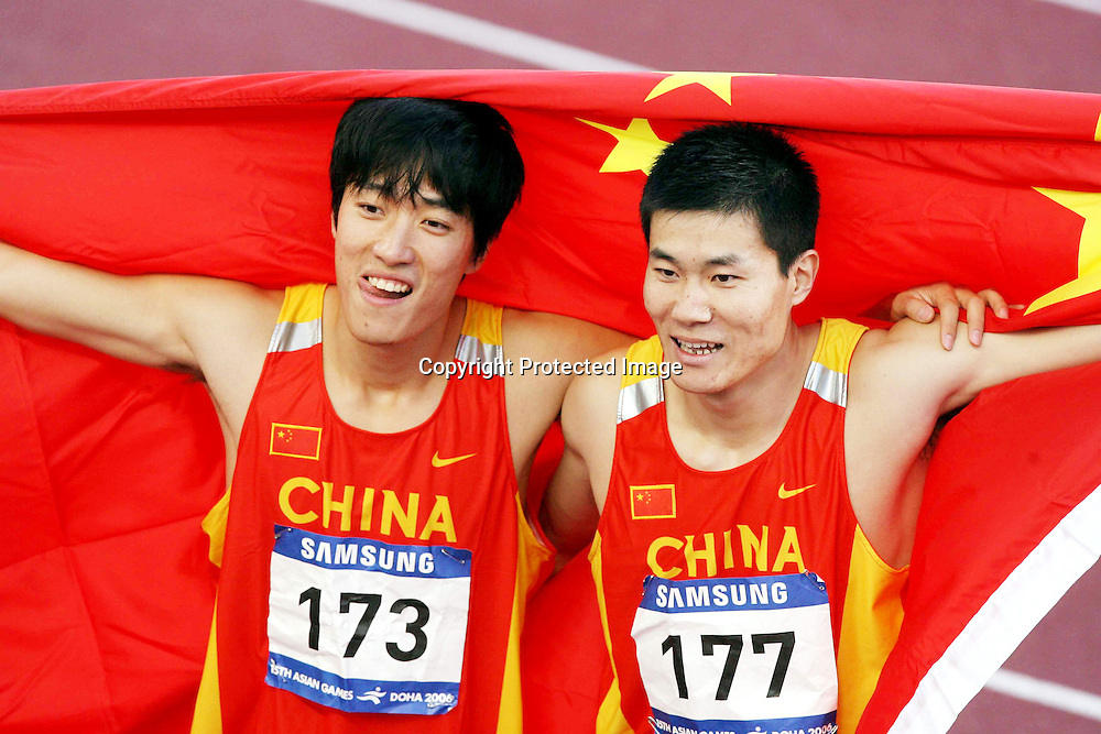 Dec 12, 2006, Doha, Qatar, China's Liu Xiang(L) celebrates with compatriot Shi Dongpeng after their first and second finish in the men's 110m hurdles final at the 15th Asian Games. Liu won gold with a time of 13.15sec.