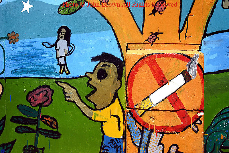 "A colorful and artistic painted wall mural depicting young children next to a ""no smoking"" sign serves as one of the unique characteristics of a street in Phnom, Penh, Cambodia."