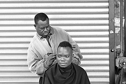JOHANNESBURG, SOUTH AFRICA – APRIL 07: Life goes on, a man gets his haircut by a street barber as MKMVA members gather nearby outside Luthuli House in support of the ANC and Zuma amidst calls for President Zuma to step down, in Johannesburg, South Africa, 07 April 2017. Businesses closed and South Africans from numerous political, religious, labour and civic groups gathered at central points across the entire country protesting against President Zuma's recent government reshuffle appointing 10 new ministers and 10 new deputy ministers including the axing of the finance minister. Photo: Dino Lloyd
