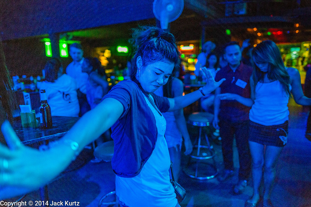 "26 SEPTEMBER 2014 - PATTAYA, CHONBURI, THAILAND: Women dance in a local bar that caters to mostly Thais in Pataya. Pataya, a beach resort about two hours from Bangkok, has wrestled with a reputation of having a high crime rate and being a haven for sex tourism. After the coup in May, the military government cracked down on other Thai beach resorts, notably Phuket and Hua Hin, putting military officers in charge of law enforcement and cleaning up unlicensed businesses that encroached on beaches. Pattaya city officials have launched their own crackdown and clean up in order to prevent a military crackdown. City officials have vowed to remake Pattaya as a ""family friendly"" destination. City police and tourist police now patrol ""Walking Street,"" Pattaya's notorious red light district, and officials are cracking down on unlicensed businesses on the beach.     PHOTO BY JACK KURTZ"