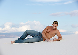shirtless man in deep thought on a sand dune in New Mexico