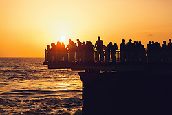 Crowd gather at sunset on a pier facing ocean, Colombo, Sri Lanka, Asia