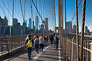 Tourists and local people stroll across Brooklyn Bridge towards Manhattan, New York City