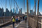Tourists and local people stroll across Brooklyn Bridge towards Manhattan, New York City