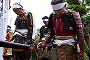 Samurai lowering theri heads during the time that the horns  (sea shels) sound in front of Samurai Fuku Taisho during the Soma Nomaoi festival. They all wear a peace of black cloth as a sign of grief for the victims of the March 11th earthquake and tsunami in Minami Soma.