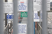 Hazard and danger warning signs on the Kaneb bulk liquid storage terminal on the River Thames at Grays, Thames Gateway