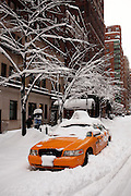 A snow-covered yellow cab New York Taxi parked on the upper east side in New York City.<br />