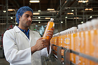 Worker examining orange juice bottle at bottling plant