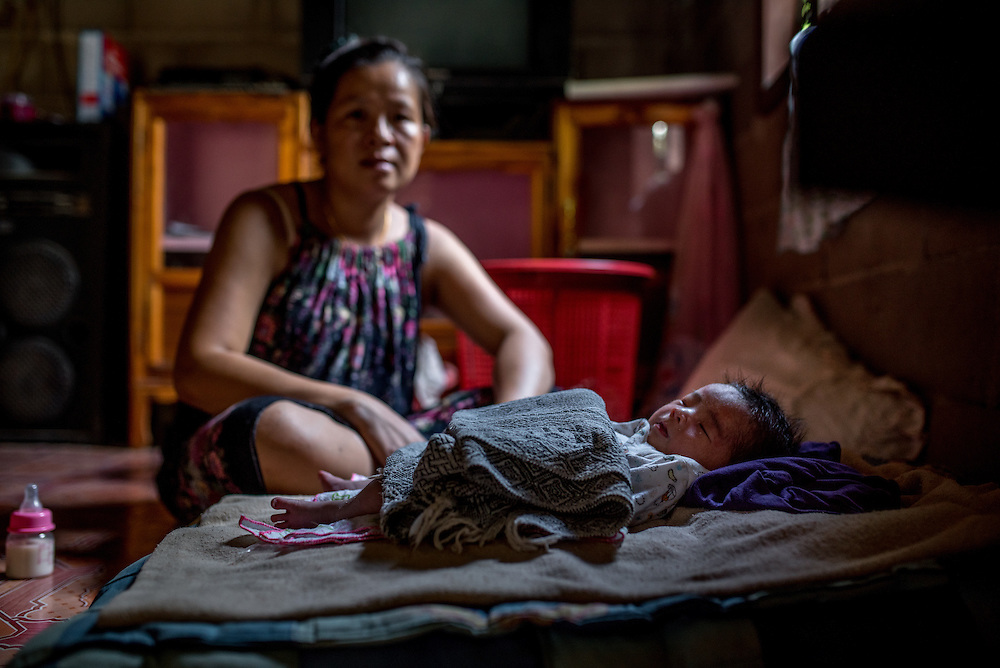 A mother watches over her 15 day old baby in the village of Khoc Kham.