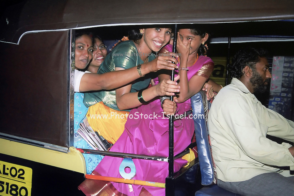 A happy overcrowded family in an auto rickshaws, India, Kerala, a state on the tropical co?st of south west India