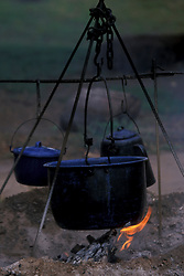 black pots of food cooking over a campfire