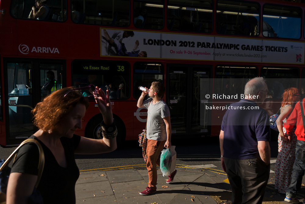 Man drinks from water bottle while walking along London street alongside a red London bus with 2012 Paralympics ad.