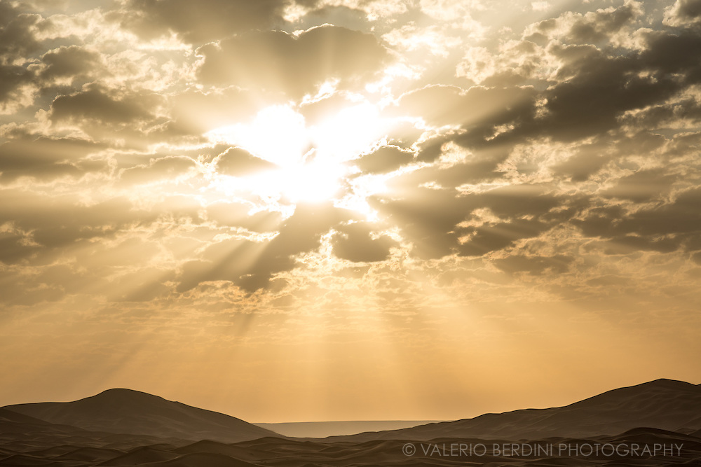 Sunrise beyond the clouds and over sand dunes in the Sahara in Merzouga. Morocco