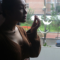 "BEJING,CHINA-SEPTEMBER 4: Lucy,Hao,24,a jewlery trader,stands near a window  in a cafe with her ""new face"" and ""new breasts"", on September 4 ,2003,in Beijing,China. While waiting for the next surgery on September 8,2003 where she'll have lipsucction on her tights,Hao keeps herself busy with shoppping and ""taking care of herself"". ..Hao sparked a  media frenzy when she announced some weeks ago that  she'll undergo  cosmetic surgery 14 times in order to enhance her  nose,hairline,eyes,jaws,neck,bottom,breats and legs.Hao believes being""pretty"" is essential in China's society to be successful ,in her case she plans to become an actress.Cosmetic clinics have poppped up all over urban China as western features have  become very popular with urban Chinese women who want to distinguish themseleves from the masses and the majority of whom is between 20-30 year old .  Hao's surgery costs USD 50,000 and reportedly is the most expensicve cosmetic surgery in China up to now..."