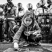 A girl writes in chalk in front of a police line during a demonstration against the state electrical utility in Miryang, South Korea.