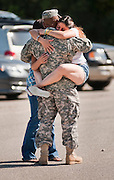 Specialist Omar Guerrero hugs his wife CeCe (right) and his daughter Stephanie in the parking lot of the San Marcos National Guard Armory on Sunday before a homecoming ceremony of Bravo Company, 1st Battalion, 141st Infantry Regiment.  The 150-man unit returned from a tour in Iraq.