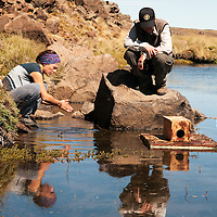 Lali Fasola and Alejandro Valenzuela, Wildlife biologists, checking traps on mink raft. Patagonia, Argentina.