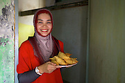 Asma Yunidar with a plate of freshly cooked Pastels.<br /> <br /> Asma runs her own snack business, making pasties, donuts, crisps and other snacks from her small home kitchen. <br /> <br /> After attending the business training she learnt how to keep her books accurately and she has now realised she earns more than her husband.