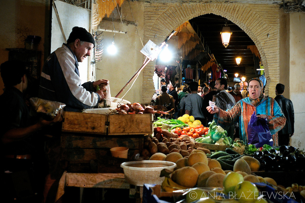 Morocco, Fez. Woman buying vegetables in the medina of Fez.
