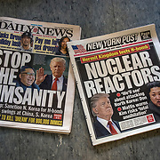 Newspaper cover headlines about H-bomb tests.<br />