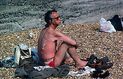 With his personal belongings and beach shingle surrounding him, a man sits on his seaside towel in soft sunlight in Dover eating a snack which is dribbling out of his mouth. The skin from many previous hours of exposure to solar radiation has left him raw and sunburned and therefore dried and dying skin is peeling in shreds on his back and shoulder. He looks like an eccentric local character who seems oblivious to the health risks that his continued sunbathing is inflicting on his bizarrely scorched body.