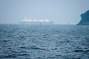 very large ship moving in the far distance along the coast near Yokosuka Japan