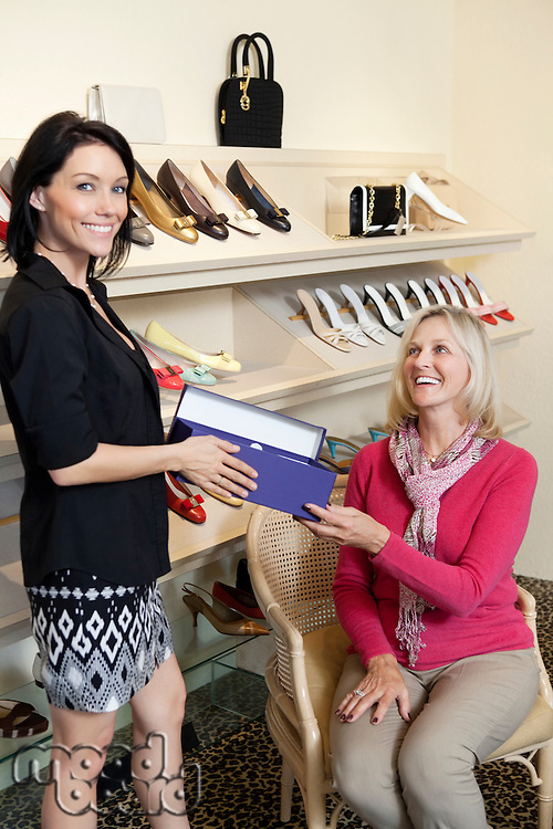 Portrait of a mid adult salesperson giving footwear box to mature female customer in shoe store