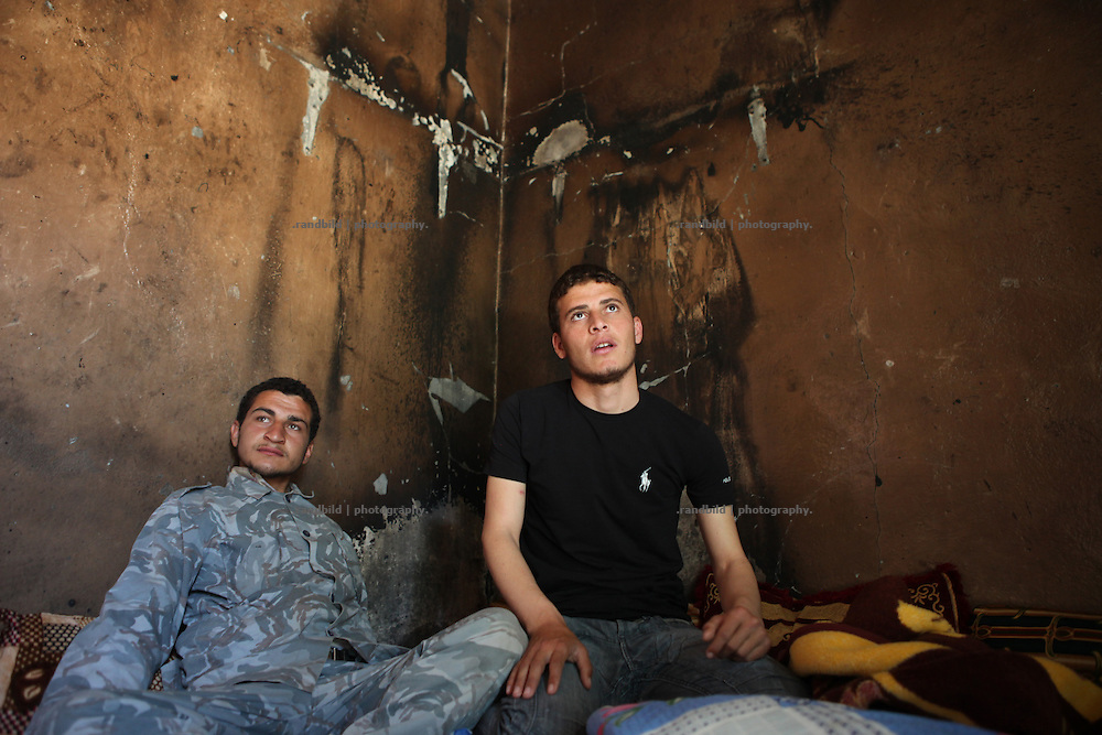 Two men sitting in a house with grime coated black walls. The village of Bashirija was beeing attacked by syrian Army in early April, leaving serveral people dead. Many houses were set on fire and livestock were shot dead by Assad loyal forces raging for two days. Later nighbours buried bodies of inhabitants hasty in a mass grave.