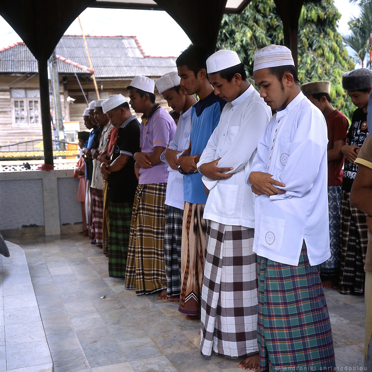 Men praying during the Friday service at the iner yard of the 300 mosque. 300-Years Mosque or Wadi Al-Husein Mosque is located at Ban Talomano, Tambon Lubosawo, 25 kms. north of Narathiwat or 4 kms. from Amphoe Bacho on Highway No. 42. As the sign outside it says, it was build in 1624 by Wan Husein, a pioneer of Due Lok Mano Village and an islamic teacher at Sano Village. The whole wood building is a combination of Javanese and local styles of art before the Arab influence.